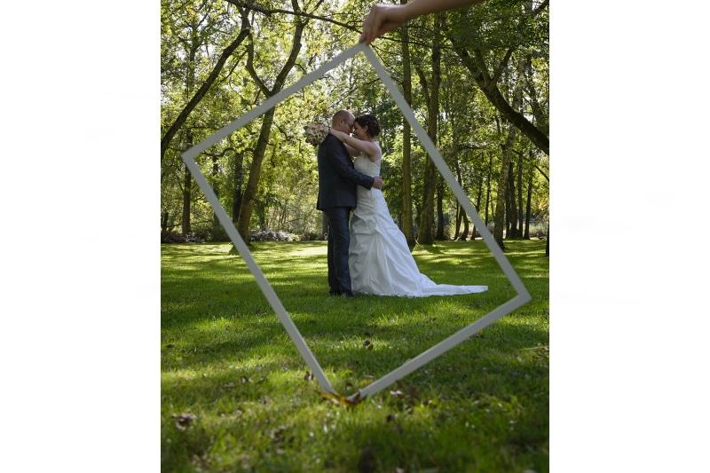 les mariés posant dans un cadre vide pendant les photos de couple